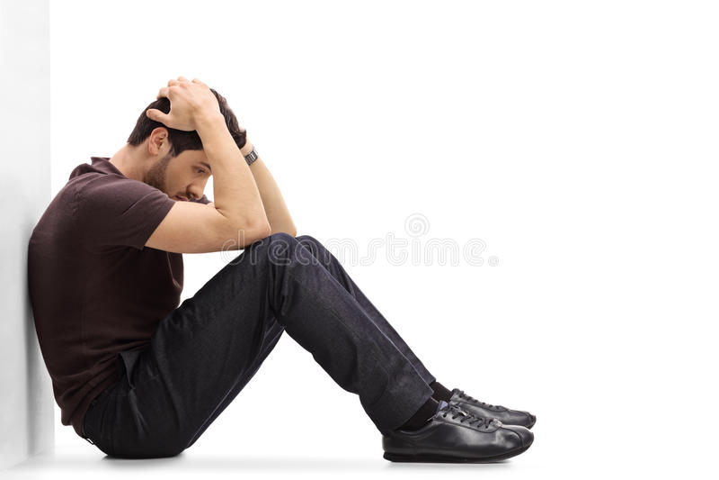 Przygnębiony mężczyzna obsiadanie na podłoga z jego kierowniczym puszkiem zdjęcie stock