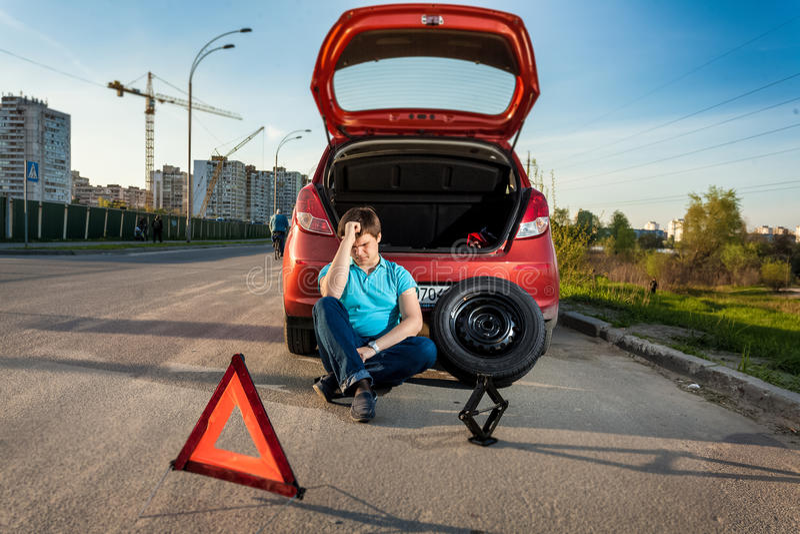 Przygnębiony mężczyzna opiera przeciw łamanemu samochodowi fotografia stock