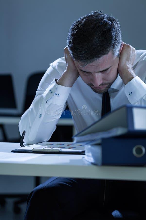 Przygnębiony mężczyzna pracuje przy nocą zdjęcie stock