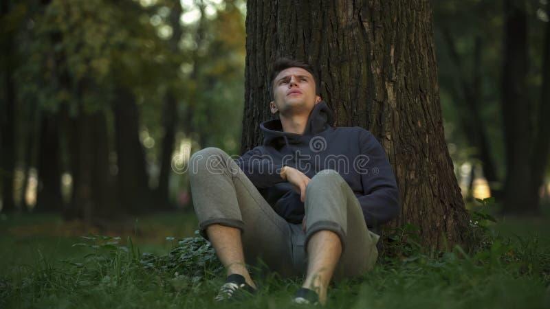 Przygnębiony mężczyzny obsiadanie pod drzewem w parku, bezrobocie problem, szykany zdjęcia royalty free