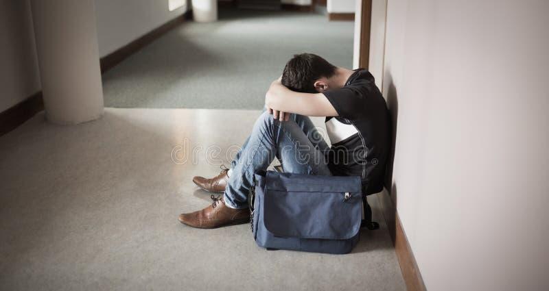Przygnębiony męski uczeń z głową na kolanach obrazy royalty free