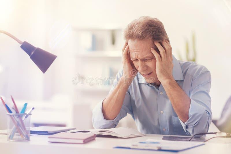 Przygnębiony męski urzędnik ma migrenę obraz royalty free
