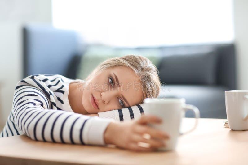 Przygnębiony młodej kobiety obsiadanie przy stołem zdjęcie stock
