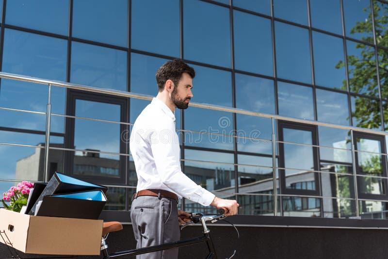 przygnębiony młody kierownik z pudełkiem osobisty materiał na bicyklu obrazy stock