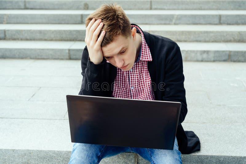 Przygnębiony młody przystojny mężczyzna siedzi outdoors i patrzeje laptop zdjęcie stock
