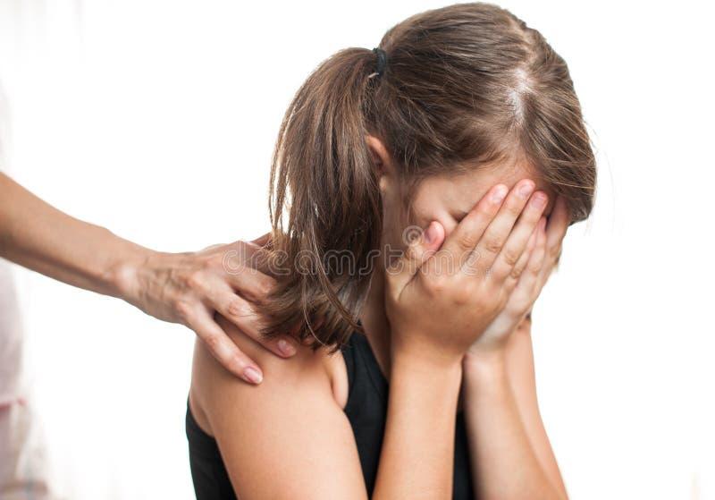 Przygnębiony nastolatka obsiadanie podczas gdy ręki przybycie od behind fotografia stock