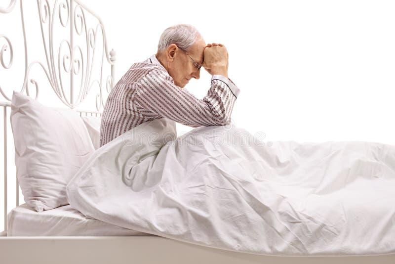 Przygnębiony starszy lying on the beach w łóżku z jego kierowniczym puszkiem fotografia royalty free