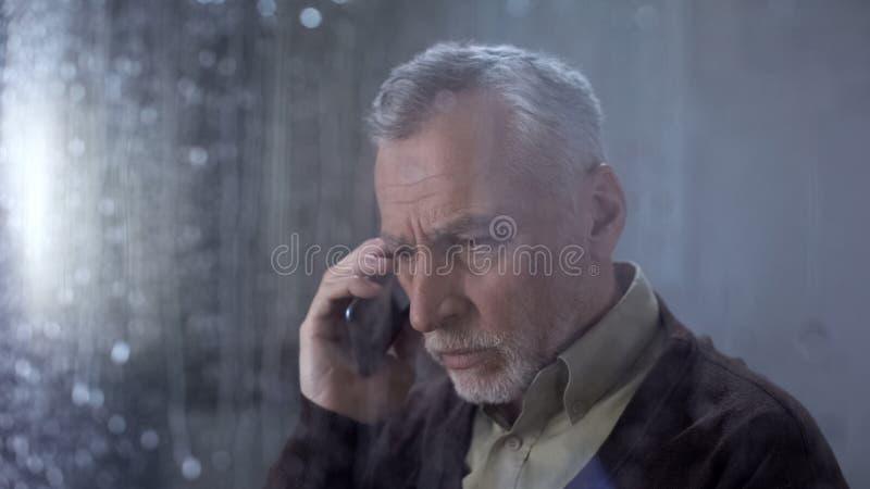 Przygnębiony starszy mężczyzna opowiada na telefonie, rodzinna komunikacja, starości samotność obrazy stock