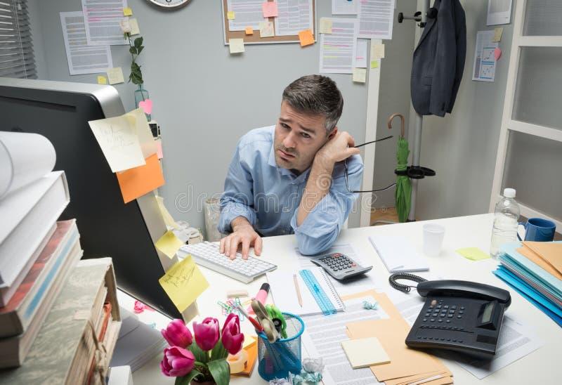 Przygnębiony urzędnik przy jego biurkiem zdjęcie royalty free