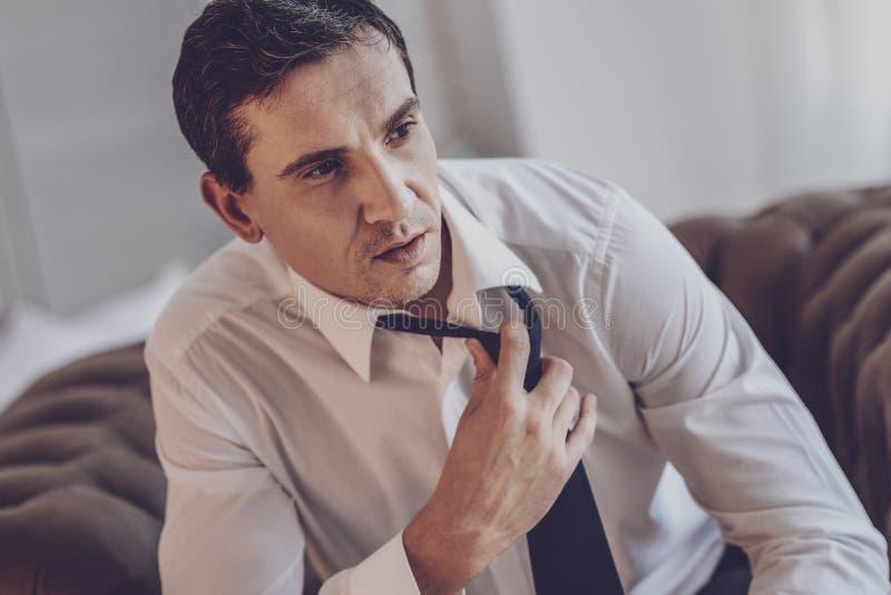 Przygnębiony zwarzony mężczyzna trzyma jego krawat obraz royalty free