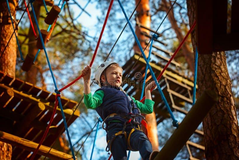 Przygoda wspina się wysokiego drutu parka - dzieciak na kursie w hełmie i zbawczym wyposażeniu fotografia royalty free