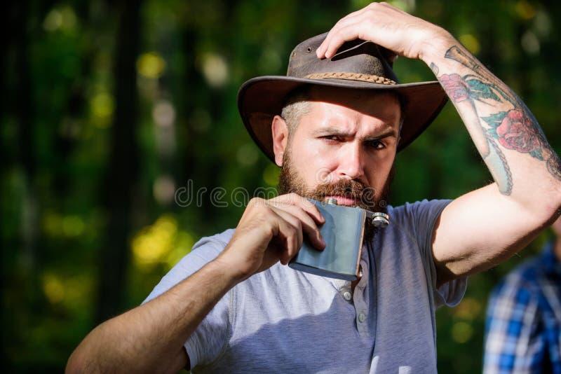 Przygoda zaczyna od pierwszy łyczka Alkoholu napój Koczowniczy mężczyzna niesie alkohol z on Faceta brutalny brodaty kowbojski na fotografia stock