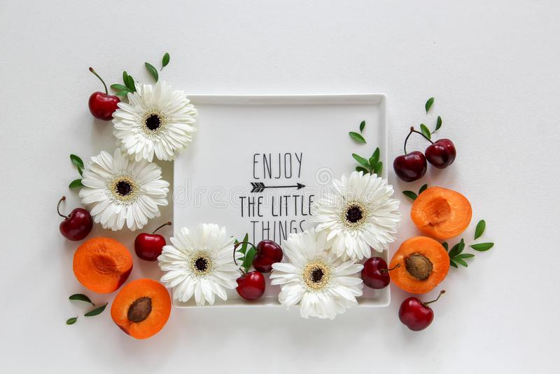 Przygotowania kwiaty i owoc na talerzu z notatką «Cieszymy się małe rzeczy zdjęcia stock
