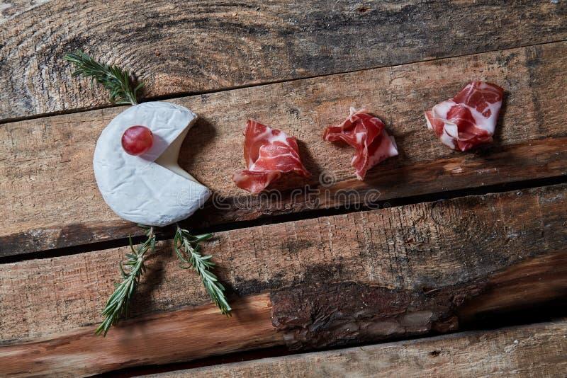 Przygotowania smakosz dobiera? zak?ski ser i prosciutto na drewnianej powierzchni Odg?rny widok obraz royalty free