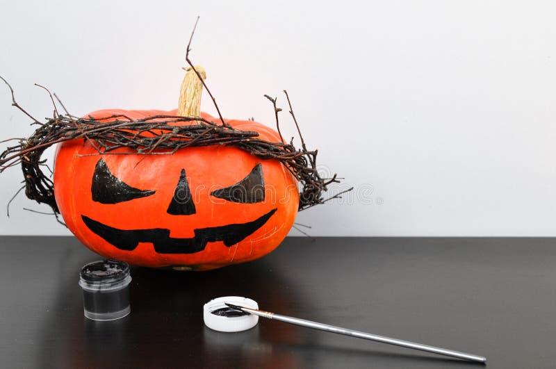 Przygotowanie dla Halloween: malująca pomarańczowa bania z czarną farbą i muśnięciem Closup Wakacyjny dekoraci pojęcie obraz stock