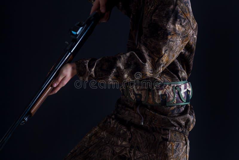 Przygotowanie dla wiosny lub jesieni polowania My?liwy w kamufla? odzie?y z pistoletem na czarnym tle odizolowywaj?cym M??czyzna  obraz royalty free