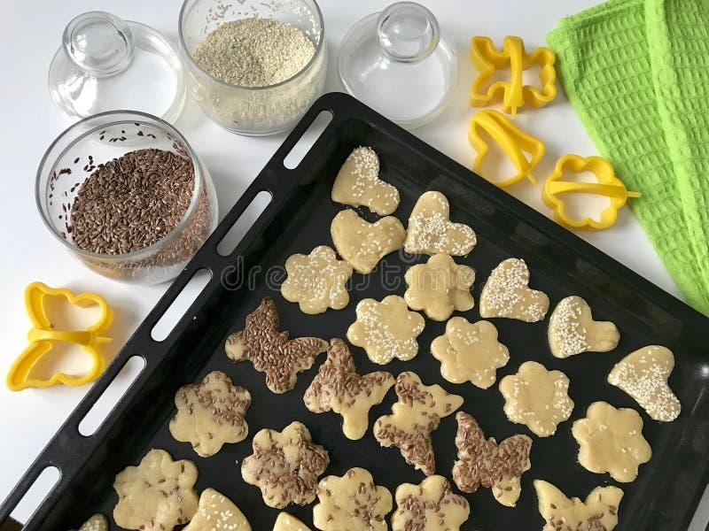 Przygotowanie domowej roboty torty Na stole jest w postaci sesam wypiekowy prześcieradło z biskwitowymi kawałkami, ciasto foremka obrazy royalty free