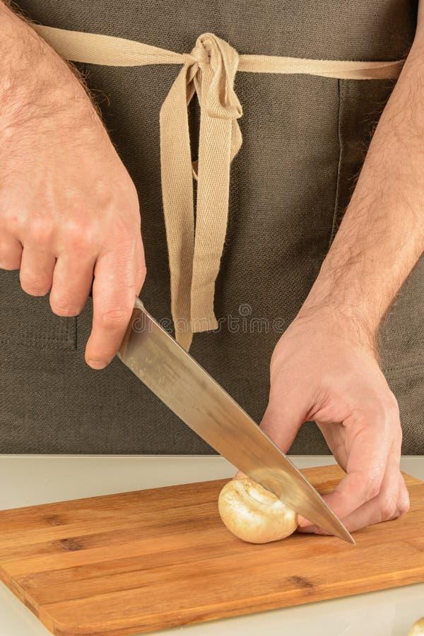 Przygotowanie jedzenie Mężczyzna w fartuchu ciie pieczarki siekać pieczarki obrazy royalty free