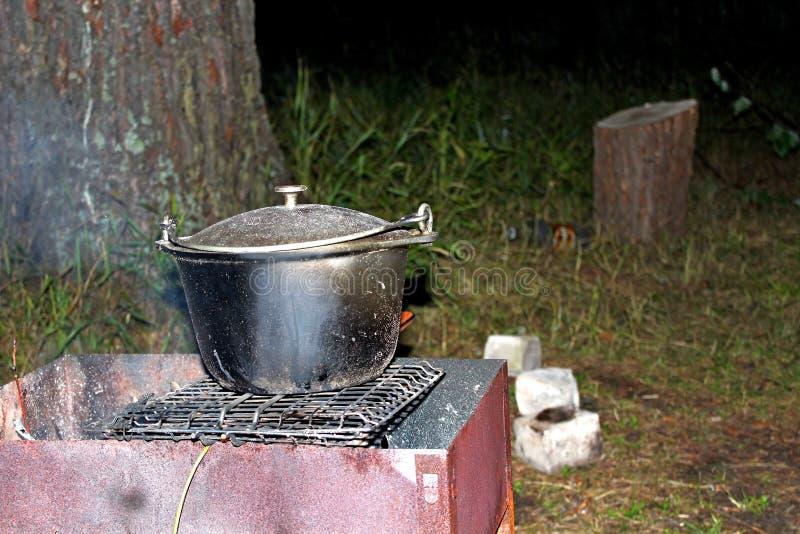 Przygotowanie jedzenie w żeliwnych naczyniach dalej otwierał ogień na lato nocy, outdoors, obrazy royalty free