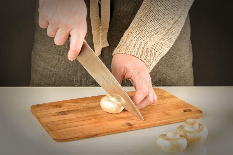 Przygotowanie jedzenie w kuchni Mężczyzna w fartuchu ciie szampinionu na drewnianej desce Piękny obrazek z winietą zdjęcia stock