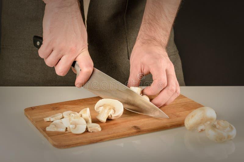 Przygotowanie pieczarki dla gotować Mężczyzna w fartuchu ciie szampinionu w cienkich plasterki zdjęcia royalty free