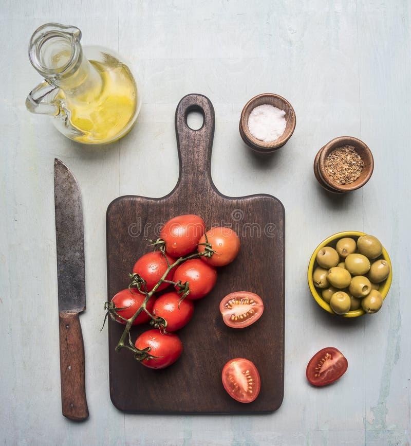 Przygotowanie sałatka z pomidorami, oliwkami, masłem i różnorodnymi seasonings, składniki wykładał wokoło tnącej deski na błękitn obrazy royalty free
