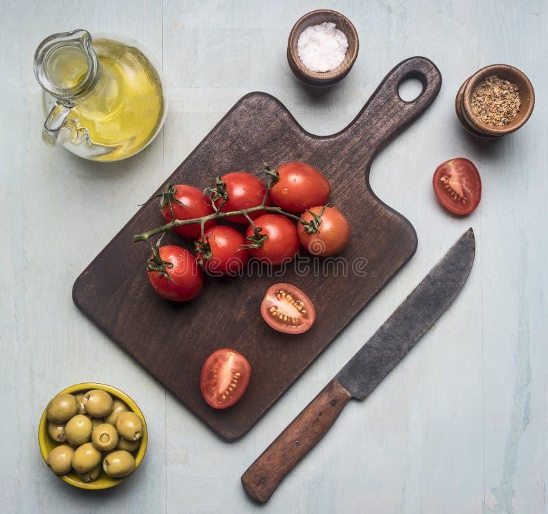 Przygotowanie sałatka z pomidorami, oliwkami, masłem i różnorodnymi seasonings, składniki wykłada wokoło tnącej deski na błękitny zdjęcie stock