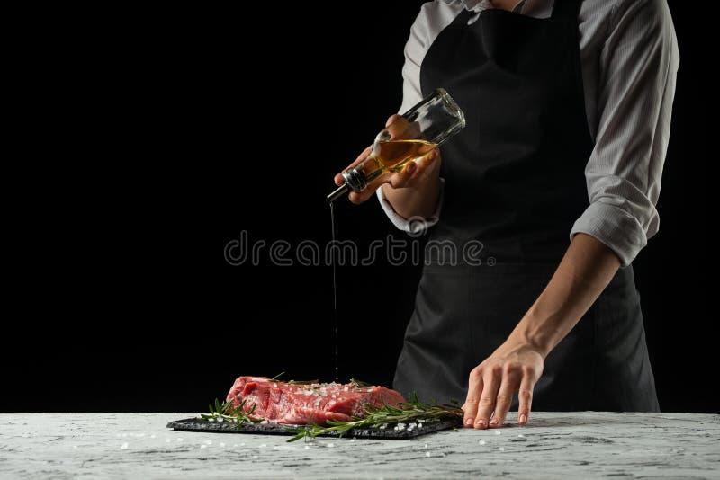 Przygotowanie szef kuchni stku kucharzem Przygotowanie świeża wołowina lub wieprzowina Horyzontalna fotografia z ciemnego czerni  obraz royalty free