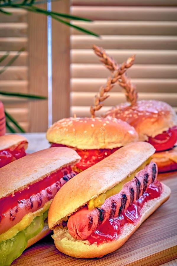 Przygotowywać domowej roboty hot dog z musztardą, ketchupem, zalewami i smażyć cebulami na drewnianym stole, Hamburgery w tle obrazy royalty free