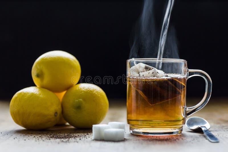 Przygotowywać gorącej czarnej herbaty z cytrynami Relaks, śniadanie i zdrowia pojęcie, zdjęcie royalty free