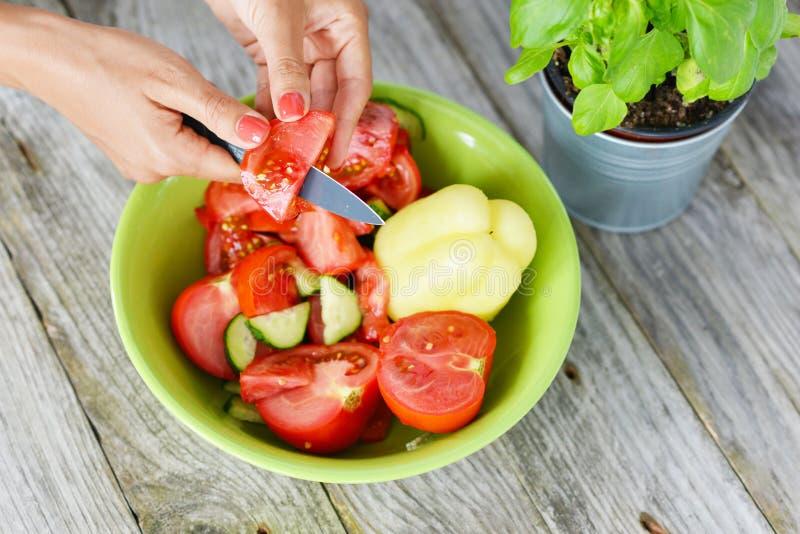 Przygotowywać zdrowej sałatki od świeżego warzywa, kobieta tnących pomidorów, pieprzy i ogórków, obrazy stock