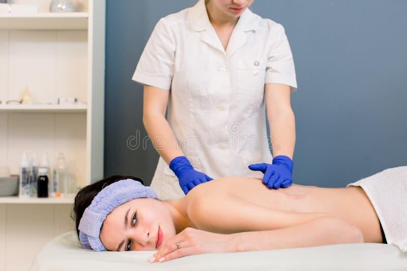Przygotowywa dla masażu - nafciany dolewanie na kobieta plecy w zdroju wellness centrum Organizacja zawodowa masaż piękna dziewcz obrazy stock
