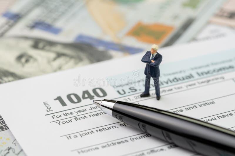 Przygotowywa dla podatek uległości okresu pojęcia, miniaturowi ludzie sukcesu biznesmena ufnej pozycji z piórem na 1040 USA jedno obrazy royalty free