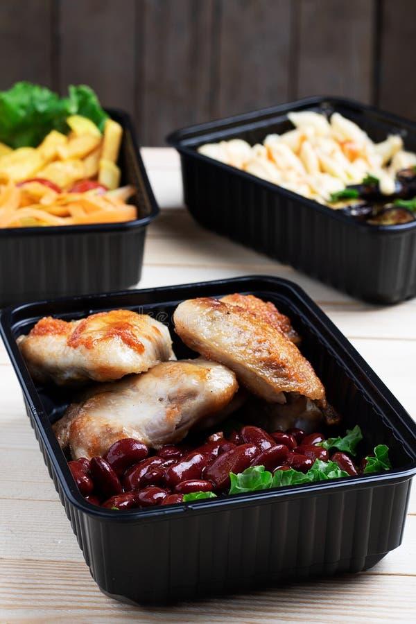 Przygotowywa posiłek, zbiorniki z, czereśniowego pomidoru i mikro greenss jeść, pieczonych kurczaków skrzydłami i surowymi warzyw fotografia royalty free