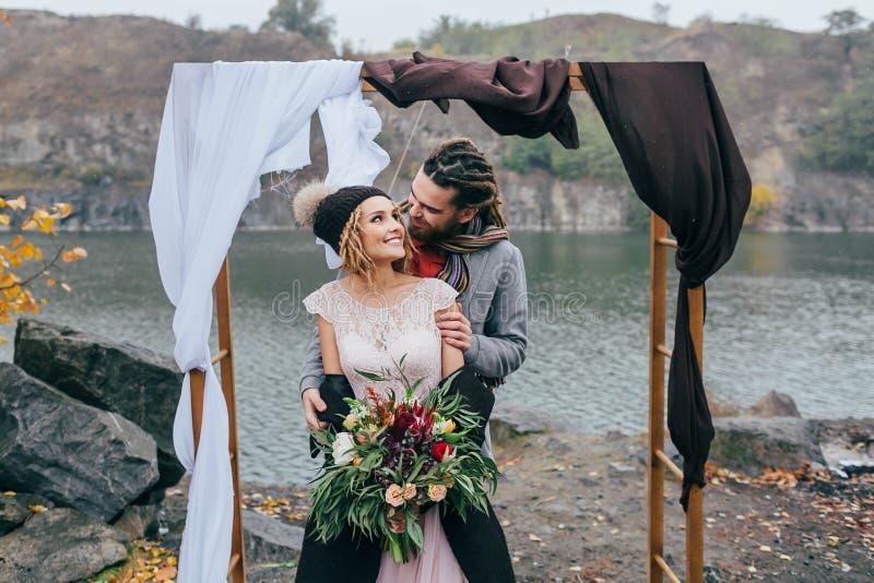 Przygotowywa tenderly obejmować jej pięknej panny młodej obok behind Jesieni ślubna ceremonia w wieśniaka stylu outdoors Szczęśli fotografia royalty free