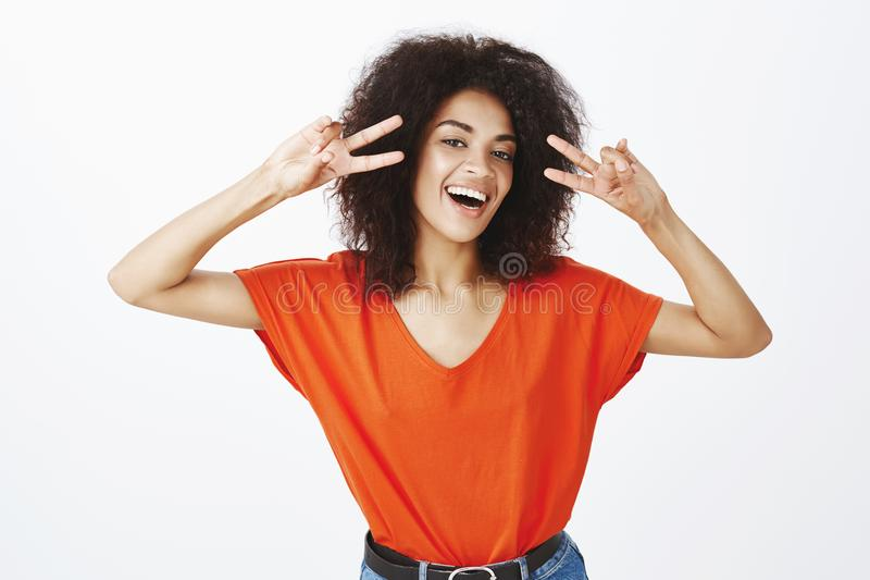 Przygotowywający badać pozytywne emocje dzisiaj Szczęśliwa beztroska atrakcyjna kobieta z ciemną skórą i afro fryzurą ono uśmiech obrazy royalty free
