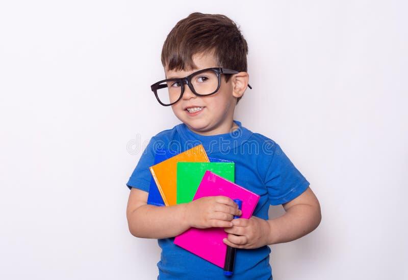 przygotowywaj?cy szkolny ucze? Dziecko materiały dla szkoły Dzieciak z notatnikiem i pióro w rękach zdjęcia stock