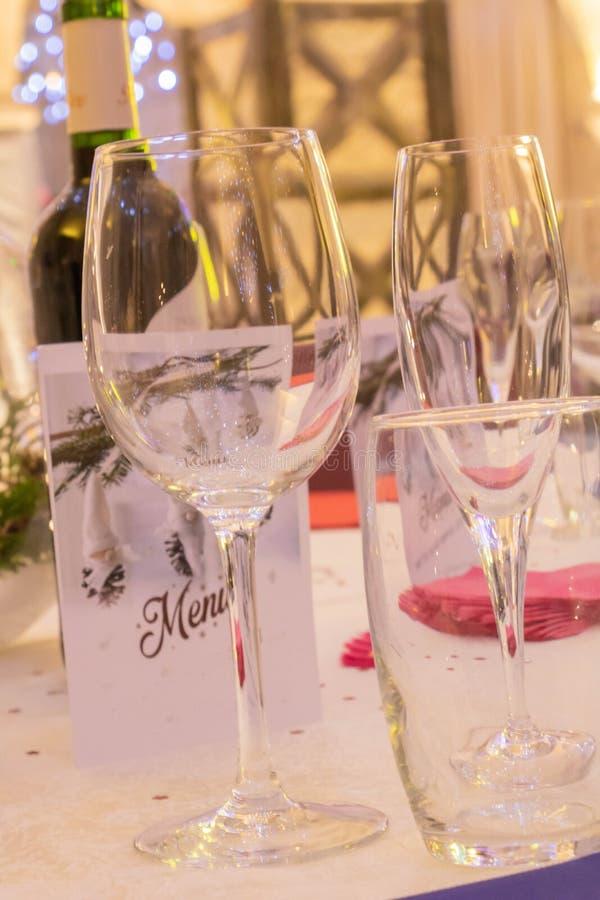 Przyjęcia i przyjęcia stół z wina szkłem, wodnym szkło, szampana szkło, menu i butelka wino, obraz royalty free