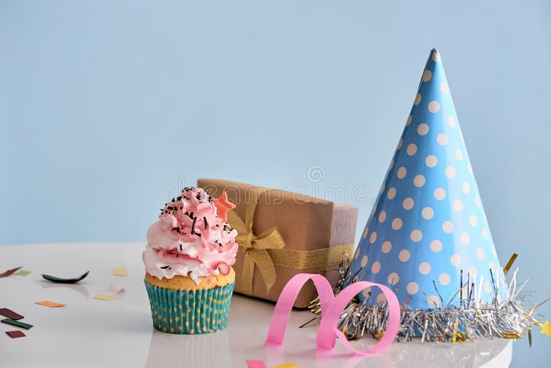 Przyjęcia urodzinowego tło z babeczką, partyjnym kapeluszem i teraźniejszością, obraz royalty free