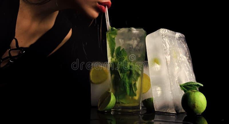 Przyjęcie i wakacje Koktajl z kostką lodu dla młodej dziewczyny na czerni kobieta napoju mojito z wapnem i obrazy stock