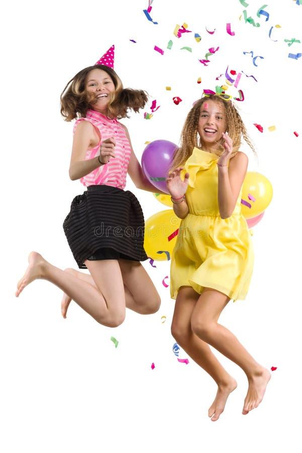 Przyjęcie nastoletnie dziewczyny, dziewczyny z balonami, confetti w świątecznych kapeluszach ma zabawę, dzieci skacze, biały tło  zdjęcie stock