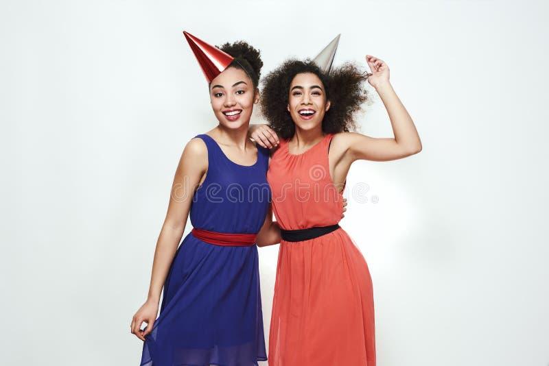 Przyjęcie urodzinowe! Dwa śliczny i młode afro amerykańskie kobiety jest ubranym lato suknie i partyjnych kapelusze świętuje urod fotografia royalty free