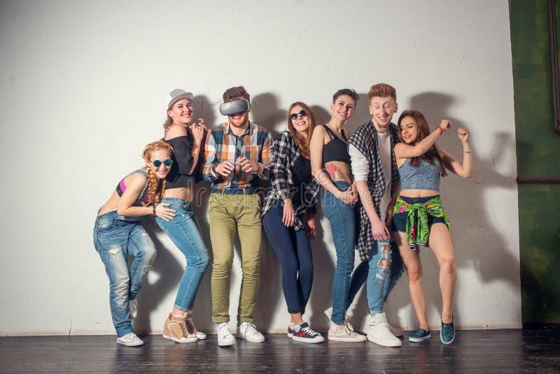 Przyjaźń, zabawa, bawi się czas - rozochoceni przyjaciele opowiada, komunikują, stojący ścianę i śmiać się indoors zdjęcia stock