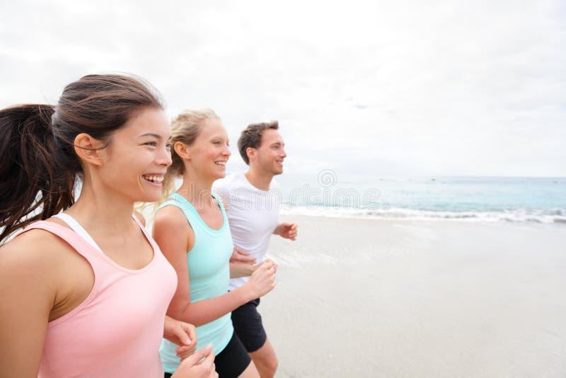 Przyjaciół biegacze jogging na plaży zdjęcia royalty free