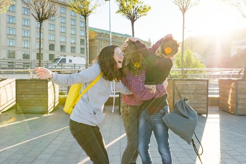Przyjaciół nastolatków ucznie z szkolnymi plecakami, mieć zabawę na sposobie od szkoły zdjęcie stock