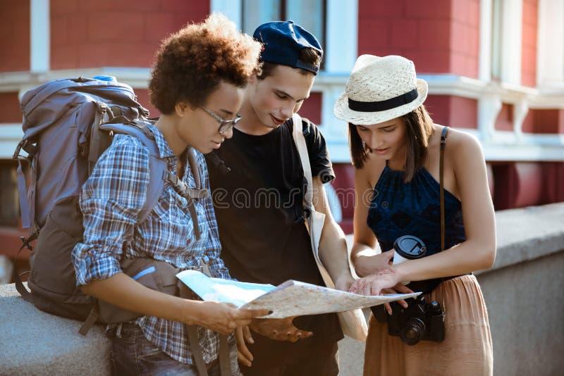 Przyjaciół podróżnicy ono uśmiecha się z plecakami, przyglądająca trasa przy mapą w ulicie zdjęcie stock