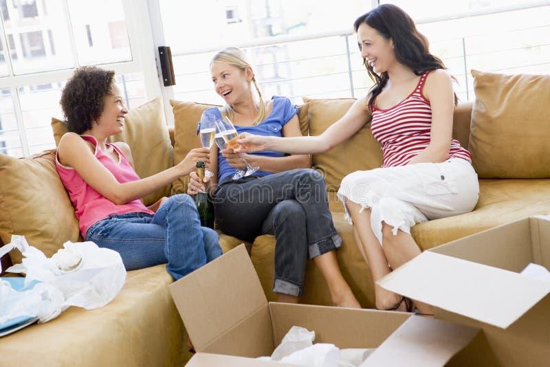przyjaciel lampki szampana, umowę plastikową dziewczyny nowego domu wznieść toast zdjęcia royalty free