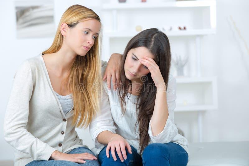 Przyjaciel pociesza boleściwego młodego żeńskiego nastolatka zdjęcie royalty free