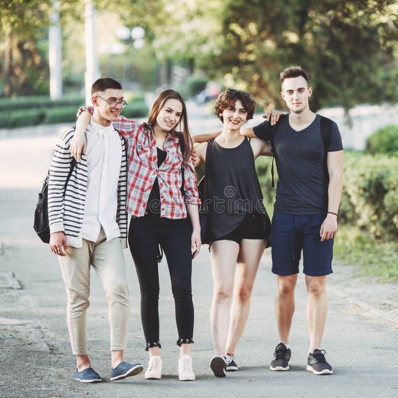 Przyjaciele ściska chodzić w mieście z plecakami zdjęcia stock