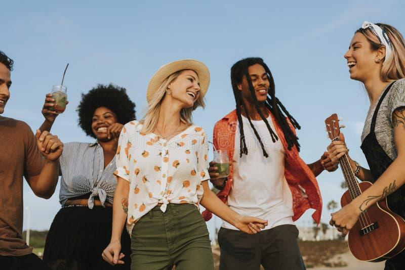 Przyjaciele śpiewa i tanczy przy plażą obraz royalty free